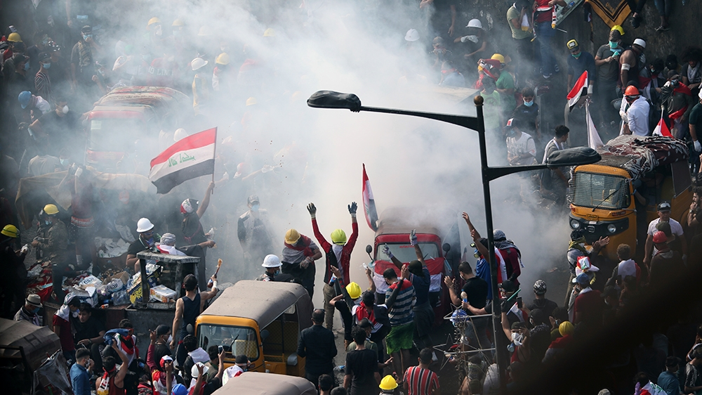 Iraqi security forces use tear gas to disperse anti-government protesters in Baghdad, Iraq, Wednesday, Oct. 30, 2019. (AP Photo/Hadi Mizban)