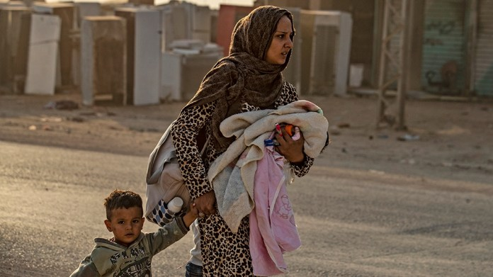 A woman flees with her children amid Turkish bombardment on Syria's northeastern town of Ras al-Ain in the Hasakeh province along the Turkish border on October 9, 2019. - Turkey launched a broad assau