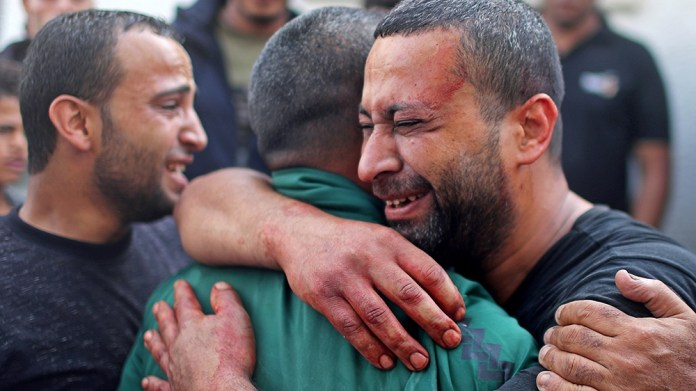 A Palestinian man, stained with the blood of his relative, is comforted as he reacts at Shifa hospital in Gaza City November 13, 2019. REUTERS/Mohammed Salem