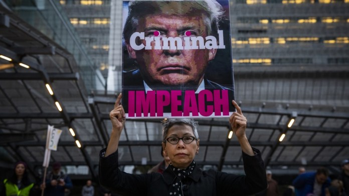 Connie Jeung-Mills of San Francisco holds a sign during a demonstration in part of a national impeachment rally, at the Federal Building in San Francisco, California. Protesters around the nation part