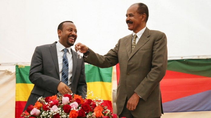 Eritrea's President Isaias Afwerki receives a key from Ethiopia's Prime Minister Abiy Ahmed during the inauguration ceremony marking the reopening of the Eritrean Embassy in Addis Ababa