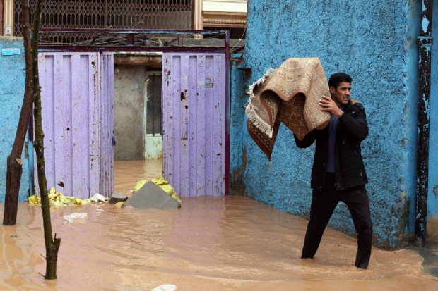 An Iranian man carries a carpet from his flooded home in the city of Khorramabad, Lorestan Province, western Iran. [Saeed Soroush/EPA]
