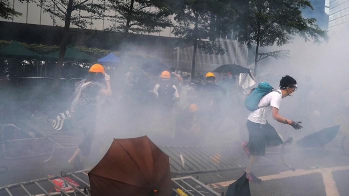 Protesters run away from the tear gas which fired by policemen during a rally outside the Legislative Council in Hong Kong, Wednesday, June 12, 2019. Hong Kong delayed a legislative session on a conte