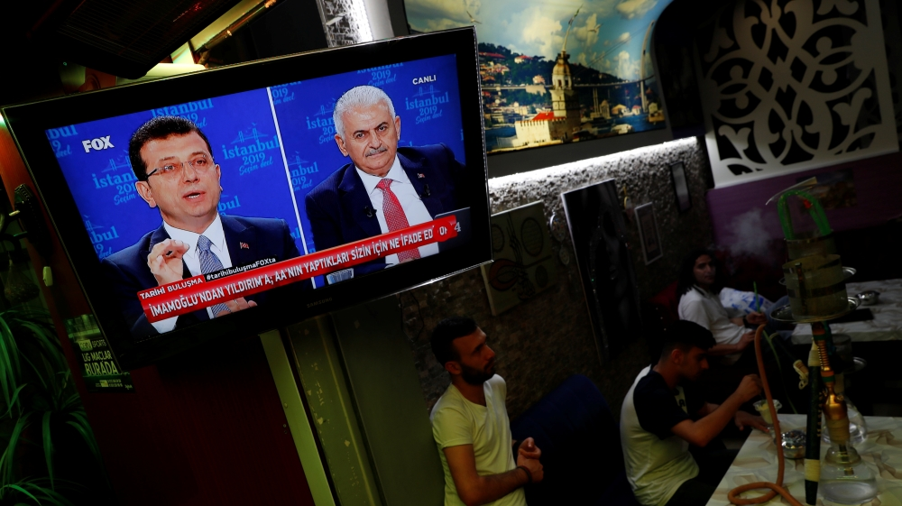 People watch a televised debate between Istanbul's mayoral candidates Imamoglu of CHP and Yildirim of AKP at a cafe in central Istanbul
