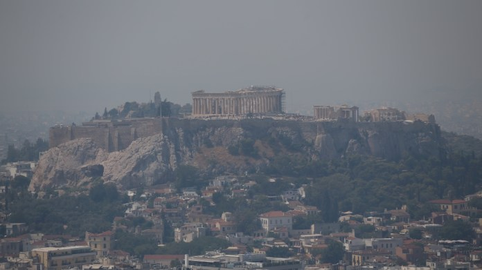 Acropolis hill with the Parthenon temple is covered with smoke from a wildfire burning the Island of Evia. in Athens