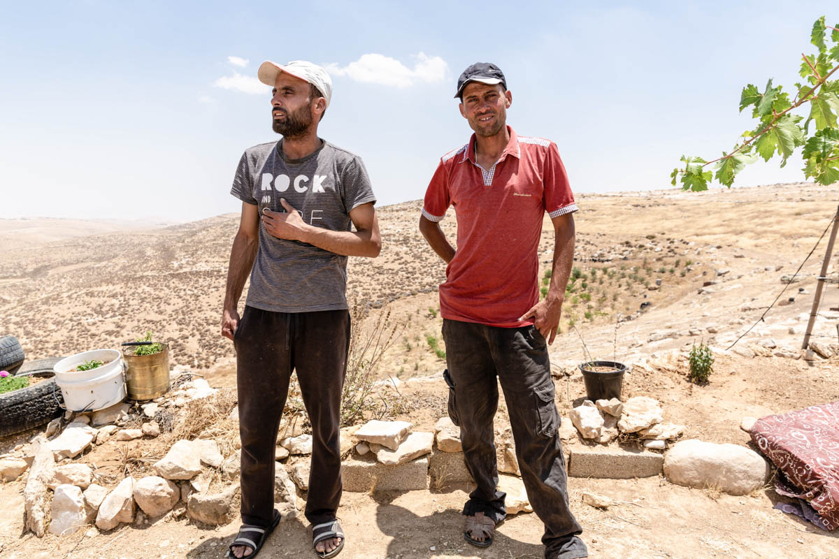 """Hael stands with his brother Radwan. As their family lost access to two-thirds of its grazing land, Hael decided to move to Yatta and get a job. """"My heart, my spirit are still here,"""" he says. [Alyona Synenko/ICRC]"""
