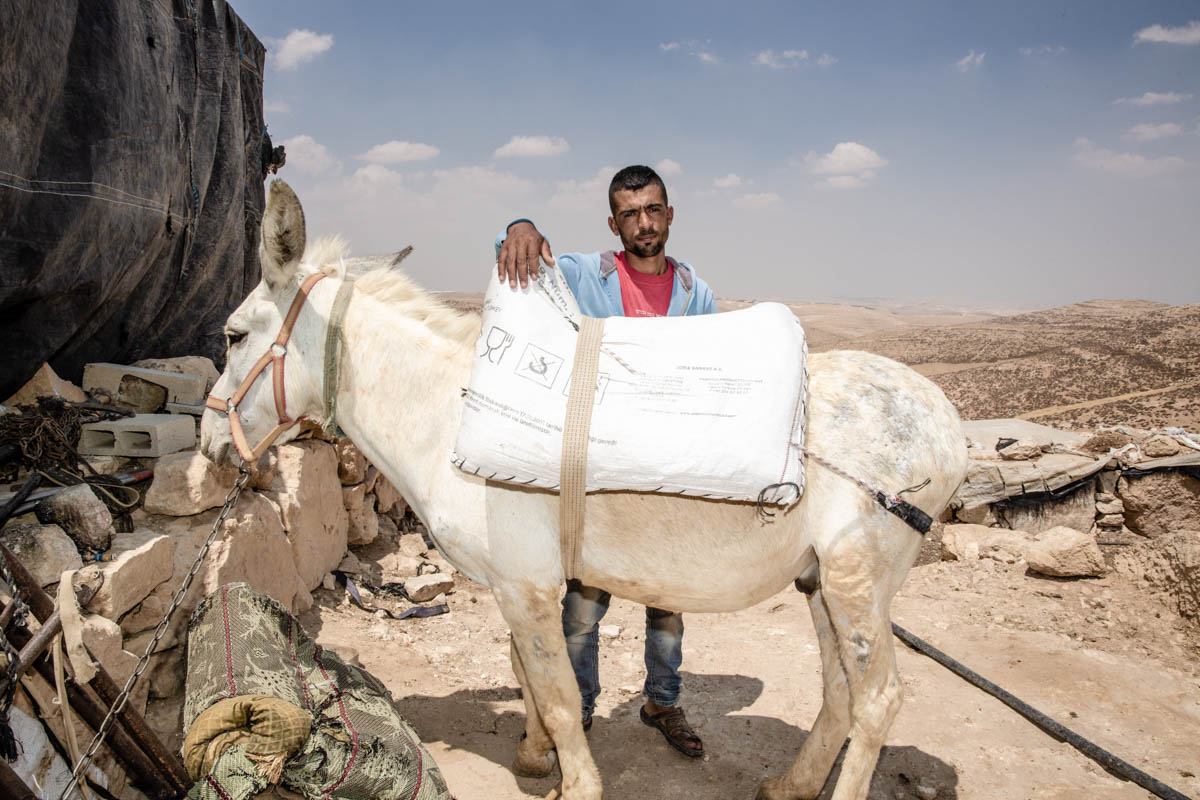 Saleh studies law at Hebron University. To get to class he takes a one-hour donkey ride through the mountains to reach the closest town, and then a bus from there. He spends an average of four hours on the road every day.  [Alyona Synenko/ICRC]