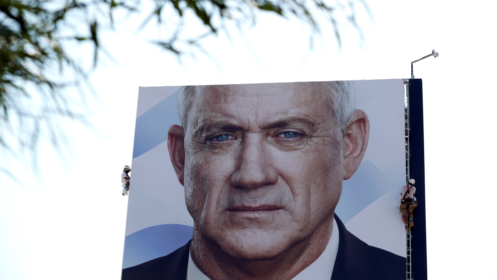 Labourers hang an election campaign banner depicting Benny Gantz, the leader of Blue and White party, in Tel Aviv, Israel September 9, 2019.
