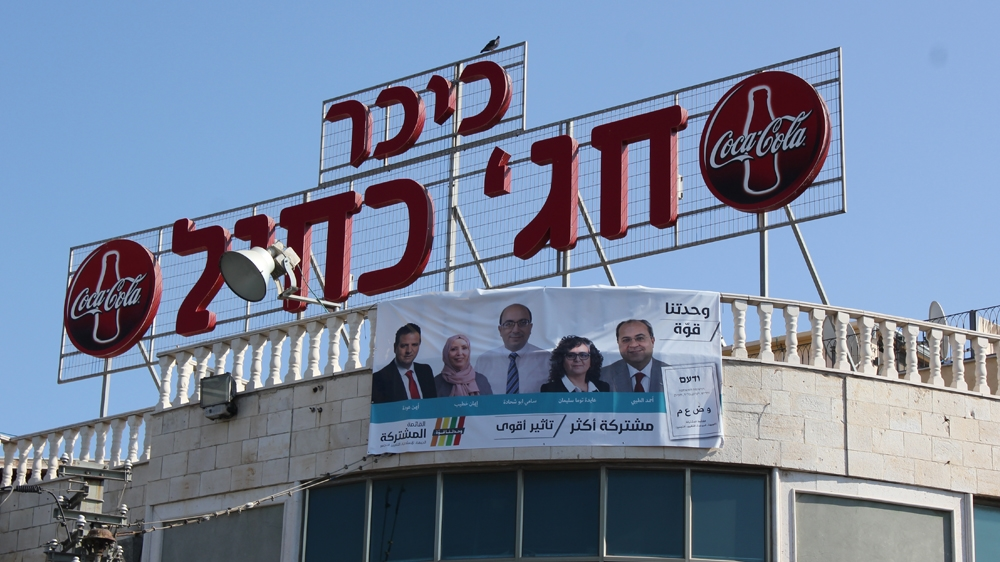 Campaign posters plastered across buildings and shop windows in Jaffa ahead of next week's election. [Arwa Ibrahim/ Al Jazeera]