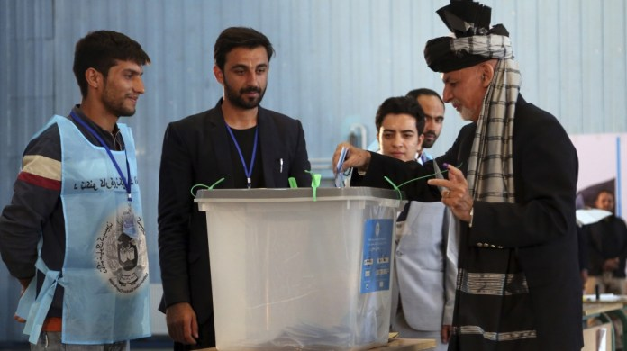 Afghan President Ashraf Ghani, right, casts his vote at Amani high school, near the presidential palace in Kabul, Afghanistan, Saturday, Sept. 28, 2019. Afghans headed to the polls on Saturday to elec