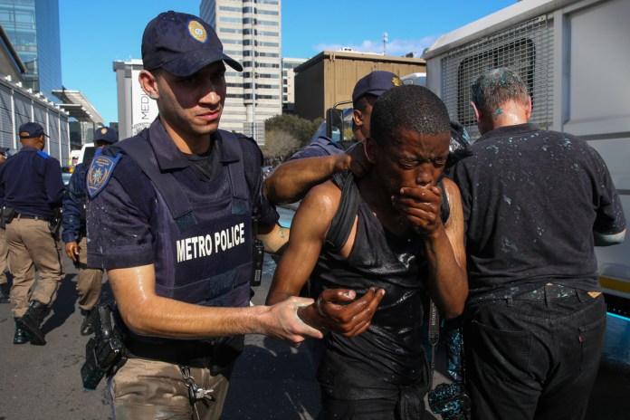 A protester is arrested near the CTICC where the World Economic Forum is taking place. Eleven students - eight women and three men - were arrested for public violence, according to the South African Police Service. [Ashraf Hendricks/Al Jazeera]