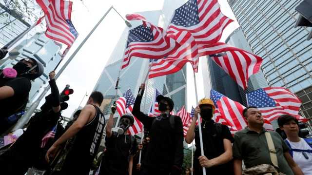 Protestors wave the U.S. flags as they march to the Consulate General of the United States at Hong Kong