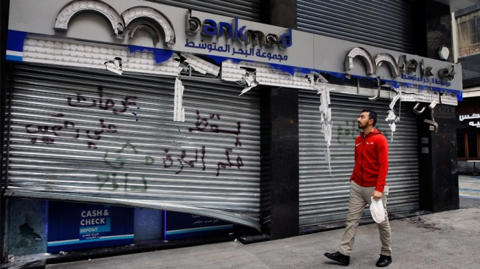 A man passes by the broken facade of the Bank MED that was smashed by anti-government protesters with a message that reads in Arabic,