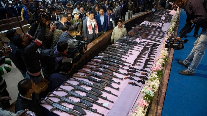 Assam state Chief Minister Sarbananda Sonowal, center, inspects arms and ammunition handed over by cadres of different rebel groups during a surrender ceremony in Gauhati, India, Thursday, Jan. 23, 20