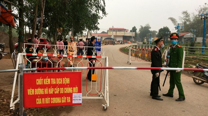 Police wearing masks guard a road checkpoint before entering the Son Loi commune in Vinh Phuc province, Vietnam, on Thursday, Feb. 13, 2020. 0fficial media reported that the Son Loi commune with 10,00