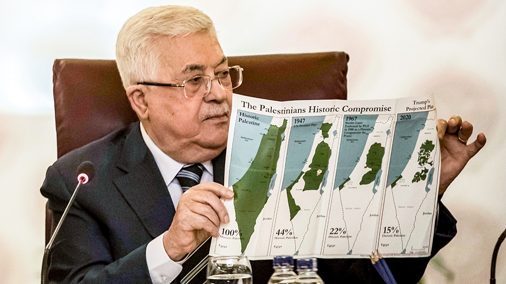 Palestinian president Mahmud Abbas holds a placard showing maps of (L to R) historical Palestine, the 1947 United Nations partition plan on Palestine, the 1948-1967 borders between the Palestinian ter
