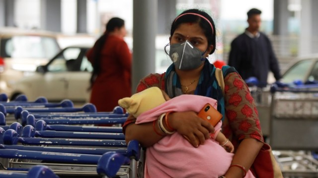 A passenger wearing a protective mask holds a baby as she waits outside an airport following an outbreak of the coronavirus disease (COVID-19), in New Delhi