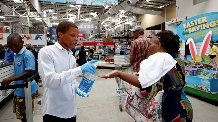 A store assistant gives people hand sanitiser as shoppers stock up on groceries at a Makro Store ahead of a nationwide 21 day lockdown in an attempt to contain the coronavirus disease (COVID-19) outbr