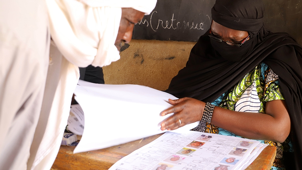 A voter (L) and an electoral official (R) checks the voters roll at a polling station during the parliamentary elections in Gao, Mali, on March 29, 2020. - Malians headed to the polls on March 29, 202