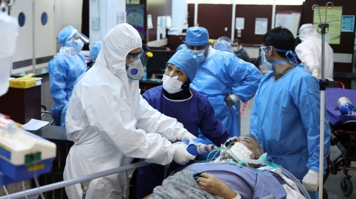 Emergency medical staff and nurses wearing protective suits, help while transferring a patient with coronavirus disease (COVID-19) to Masih Daneshvari Hospital, in Tehran, Iran March 30, 2020. WANA (W