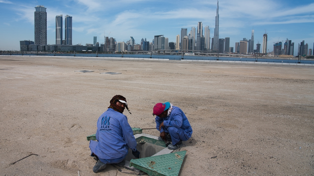 Two construction workers examine a drainage system with the Burj Khalifa, the world's tallest building, in the skyline behind them in Dubai, United Arab Emirates, Monday, April 6, 2020. Dubai, one of
