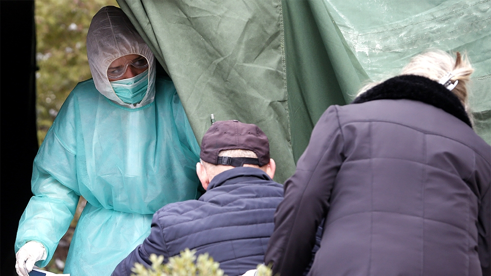 epa08321418 People wait for a corona test at a tent outside the State Hospital in Sarajevo, Bosnia and Herzegovina, 25 March 2020. Several European countries have closed borders, schools, public facil