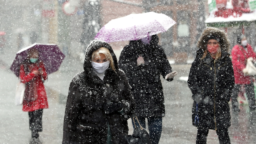 epa08334217 People wearing face masks hold up umbrellas to shield themselves from heavy snowfall in Sarajevo, Bosnia and Herzegovina, 31 March 2020. According to latest figures by WHO on 30 March, a t