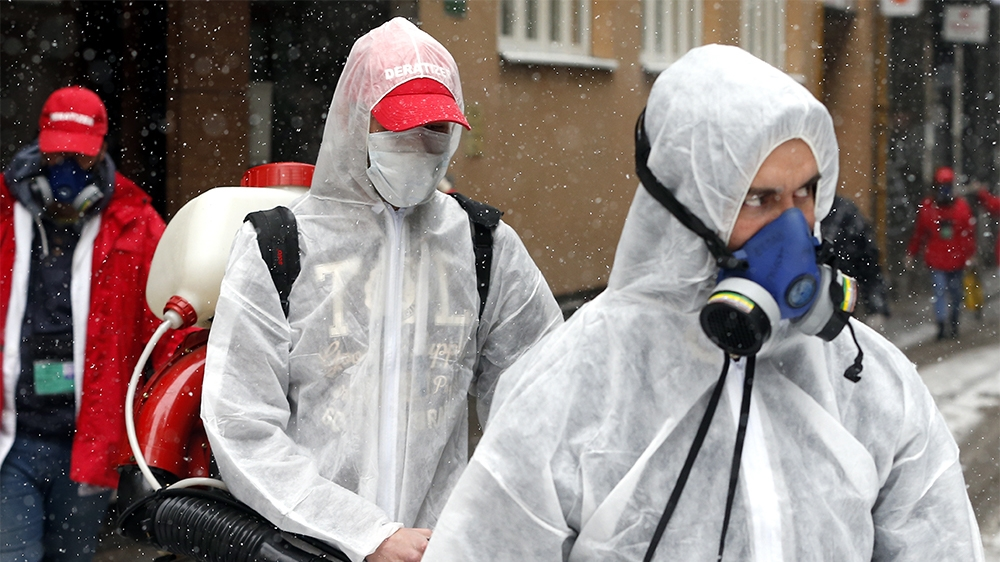 epa08318157 Employees of the local cleaning company  'Deratizer' wearing face masks with filters disinfect a building in Sarajevo, Bosnia and Herzegovina, 24 March 2020. Several European countries hav