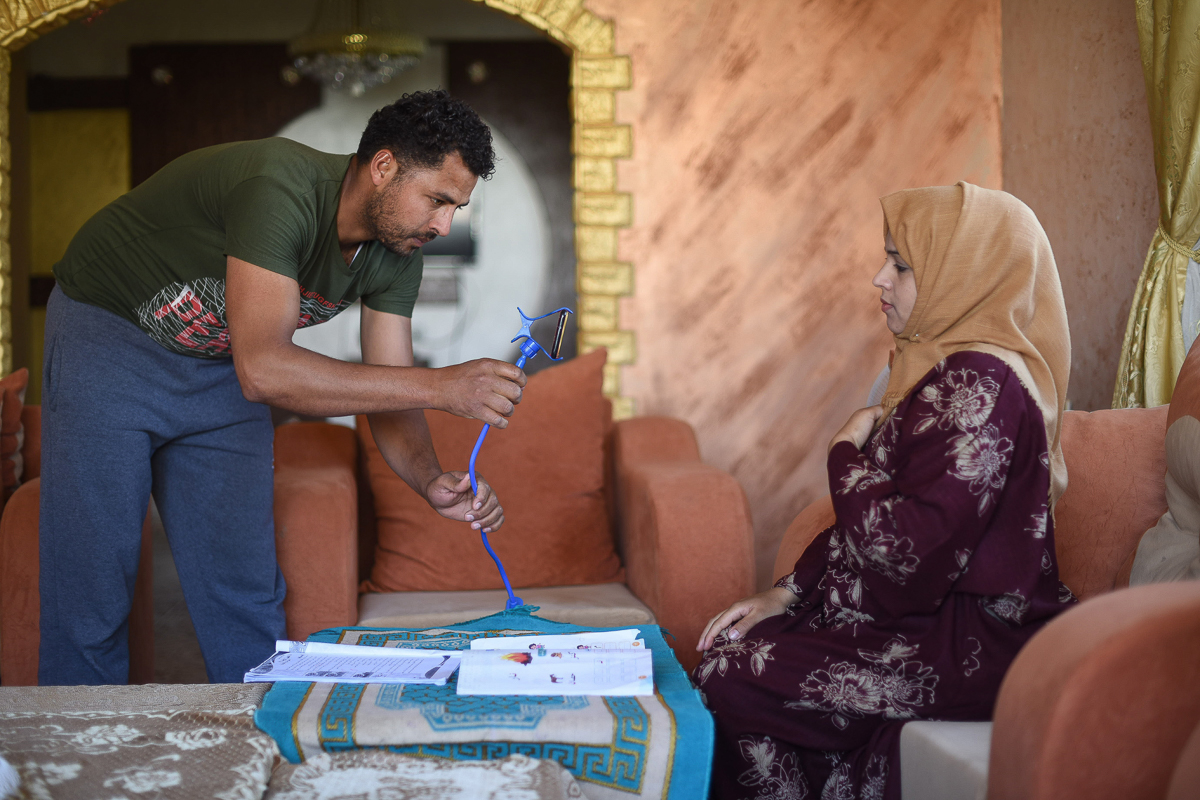 """With the help of her husband, kindergarten teacher Nidaa Abu Dabha, 30, records educational videos for her students and then sends them via WhatsApp to parents' groups. """"I am proud of my job and the creative alternatives we use to help our children receive their education under all circumstances,"""" she says. [Abed Zagout/ICRC]"""