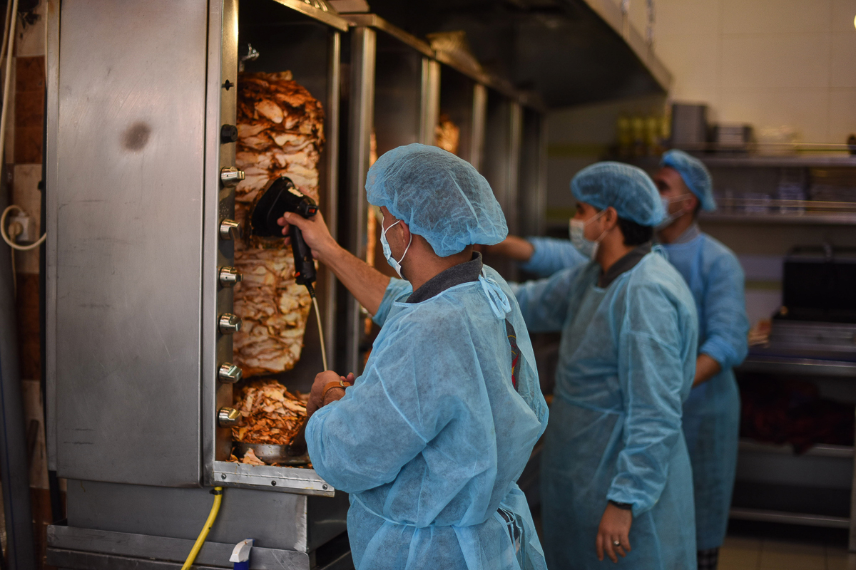 Workers at a shawarma shop work in protective clothing in Khan Younis. [Abed Zagout/ICRC]