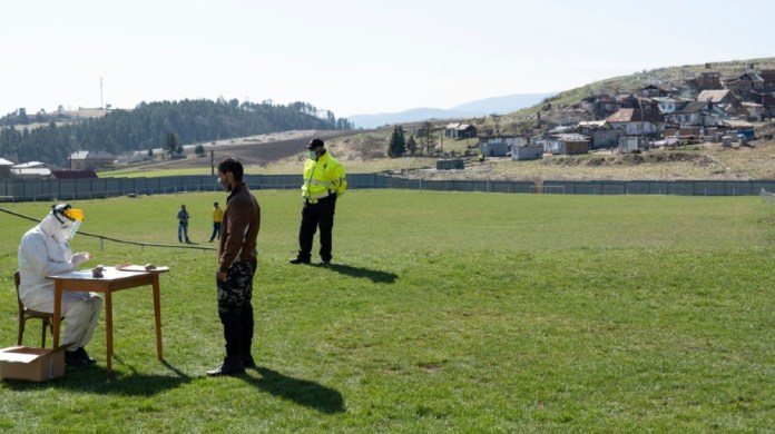 A member of the Slovak military tests a Roma people for the new coronavirus COVID-19 outside of the Roma settlement in the eastern Slovakian village of Janovce, Slovakia on April 11, 2020