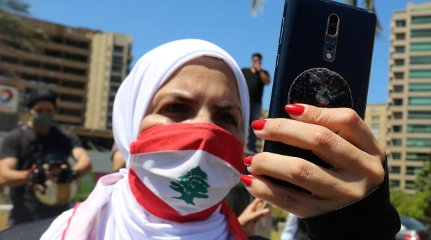 A demonstrator, wearing a face mask as a preventive measure against the spread of the coronavirus disease (COVID-19) and depicting the national flag, uses her mobile during a protest against a controv