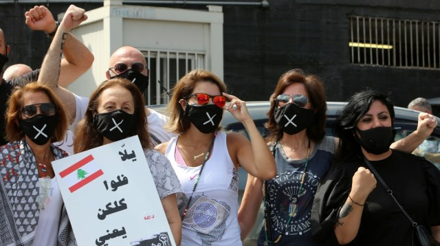 Demonstrators wearing protective masks stand together during a protest against the government's performance and worsening economic conditions near the presidential palace in Baabda, Lebanon June 25, 2
