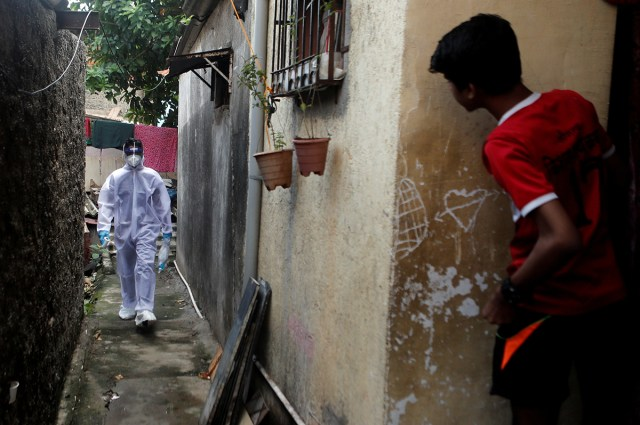 A healthcare worker wearing personal protective equipment (PPE) walks in an alley of a slum area during a check-up camp for the coronavirus disease (COVID-19) in Mumbai, India June 27, 2020. REUTERS/F