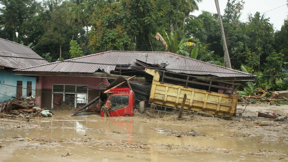 A truck is submerged in mud after flash floods swept through Radda Village, as several people were killed and dozens remain missing in North Luwu in Sulawesi