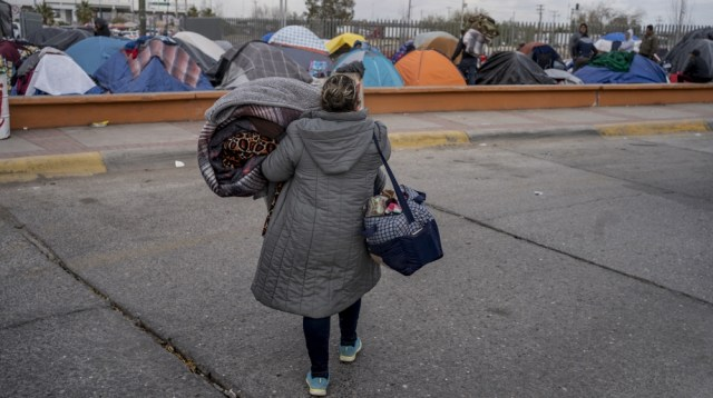 A woman carries belongings to a different part of the campsite near US ports of entry at Chamizal Park on December 19, 2019 in Ciudad Juarez, Mexico. In the mud and biting cold of a makeshift camp in