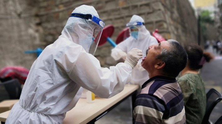 ISO Certificate Medical worker collects swab from a man to conduct free nucleic acid tests for residents in the residential compound in Urumqi