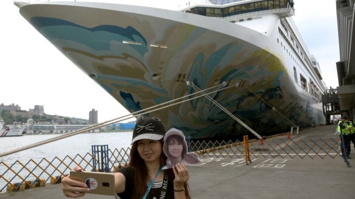 A woman takes a selfie in front of the Explorer Dream cruise ship, in Keelung