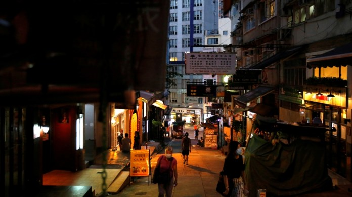 People wearing protective face masks walk at Mid-Levels Central, following the coronavirus disease (COVID-19) outbreak in Hong Kong