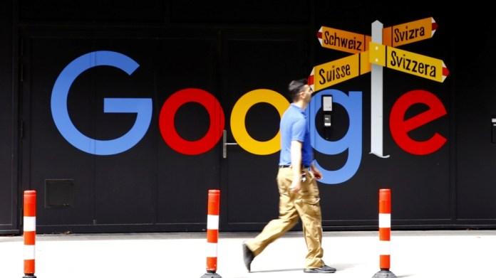 A man walks past a logo of Google in Zurich