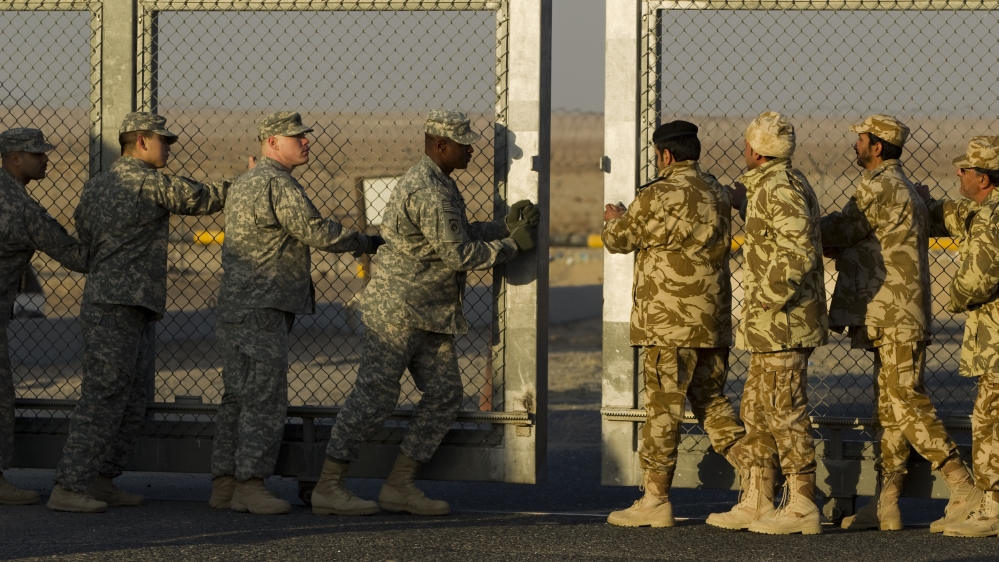 Kuwaiti and U.S. soldiers close the border gate after the last vehicle crossed into Kuwait during the US miltary's withdrawal from Iraq