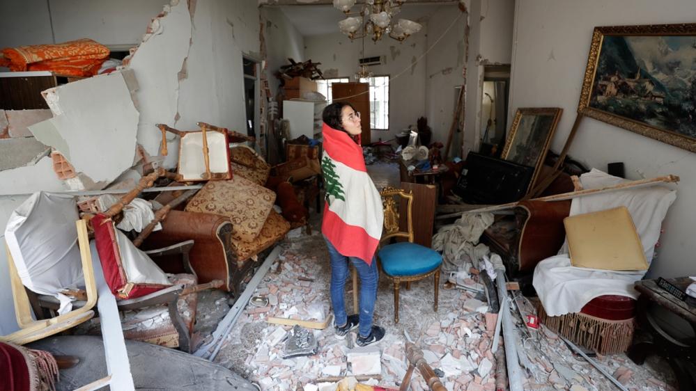 جمعرات ، 6 اگست ، 2020 کو لبنان کے بیروت ، ساحل سمندر میں منگل کے روز ہونے والے دھماکے کے بعد ، لبنان کے قومی پرچم میں لپیٹے ہوئے ، فرح محمود اپنے والدین کو اپارٹمنٹ تباہ کرنے کی جانچ کررہی ہیں۔