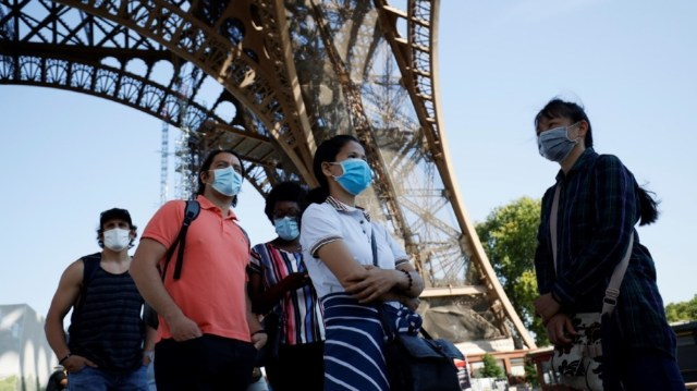 Visitors wearing protective facemasks queue as they wait for the partial reopening of Eiffel Tower on June 25, 2020, in Paris, as France eases lockdown measures taken to curb the spread