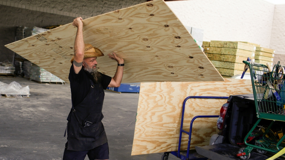 Paul Humphrey, of New Orleans, loads plywood into his truck, to board a friend's home in preparation for the arrival of hurricanes Marco and Laura, which are forecasted to move onshore Monday and Thur