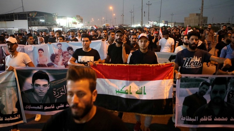 demonstrators hold national flags and posters of protesters who were killed during previous demonstrations, in Basra, Iraq.