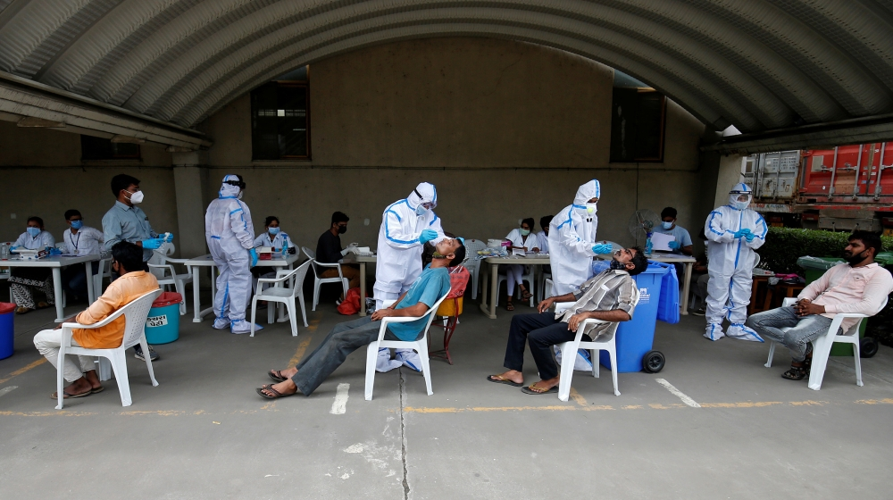Healthcare workers wearing personal protective equipment (PPE) take swabs from flour mill workers, amidst the coronavirus disease (COVID-19) outbreak, in Moriya village on the outskirts of Ahmedabad,