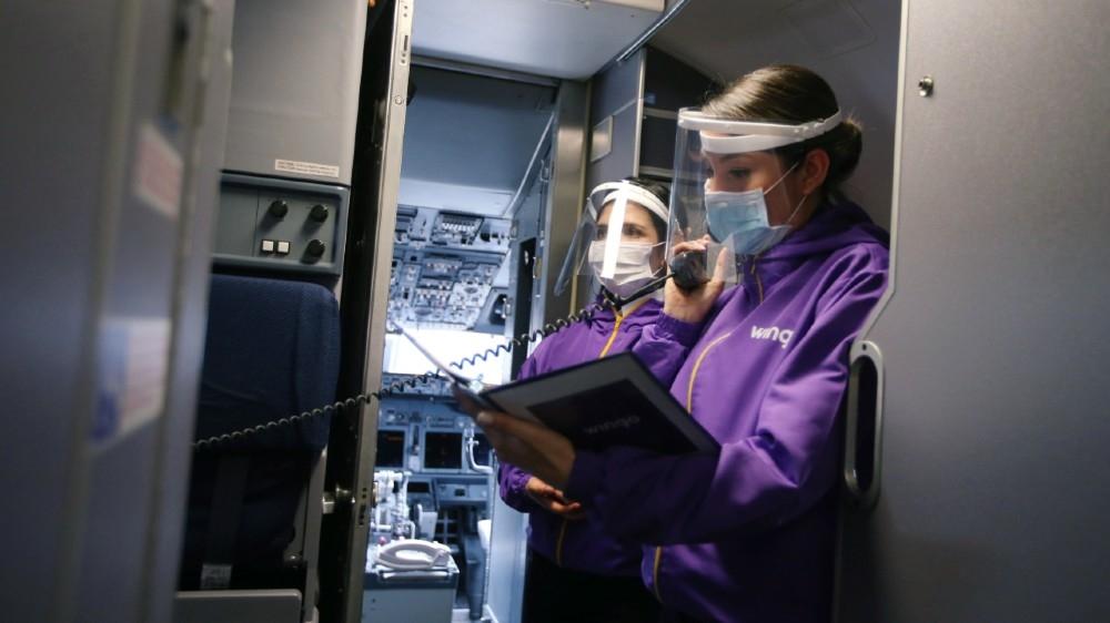 کورونا وائرس بیماری (COVID-19) کی وبا کے دوران ال ڈراڈو بین الاقوامی ہوائی اڈے پر ہوائی جہاز کے اندر چہرے کی ڈھال اور حفاظتی ماسک پہنے ہوئے ونگو ایئر لائنز کے ملازمین کو ایک ہوائی جہاز کے اندر دیکھا جاتا ہے۔