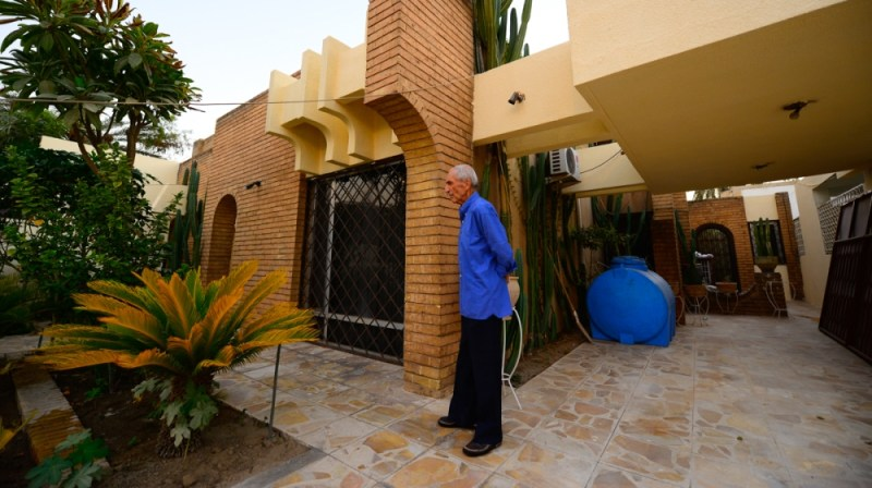 Waleed Ahmed looks out on his garden at his 1970s home in Baghdad's Harthiya neighborhood. Few of the new buildings include gardens, which are important to absorb the heat during sweltering summer day