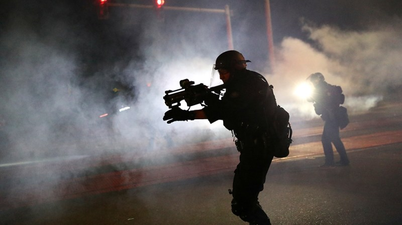 Portland Police officers disperse a crowd of protesters after a Molotov cocktail was thrown on the 100th consecutive night of protests in Portland, Oregon, U.S. September 6, 2020. REUTERS/Caitlin Ochs