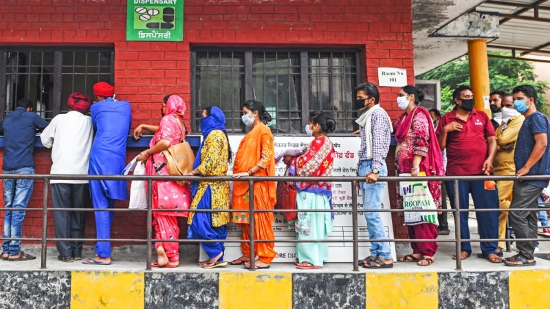 People stand in a queue as they wait for their turn to collect test reports for the COVID-19 coronavirus, at a civil hospital in Amritsar on July 17, 2020. Coronavirus cases in India passed one millio